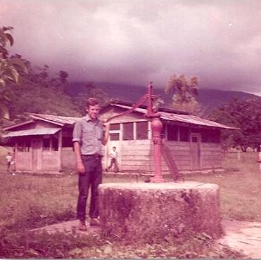 Me pumping drinking water from a well in front of the school where my wife Maria taught school 45 years ago.
