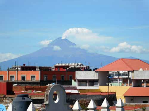 A view of Popocatépetl volcano smoking, from the rooftop terrace of our hotel